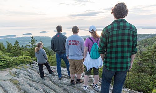 Students overlooking ocean from a mountain in Bar Harbor