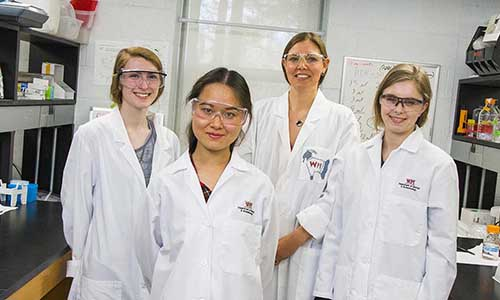 students and professor in research lab