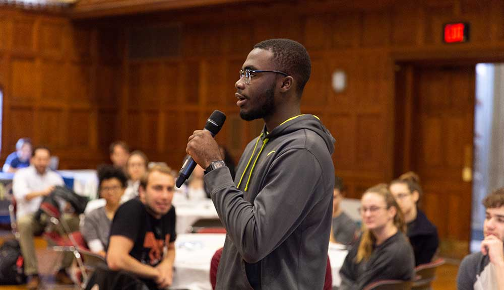 A student holding a microphone participates in the first annual Social Justice Summit on campus.