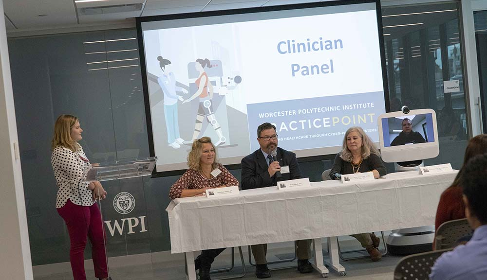 Three members of the clinician panel in discussion during a PracticePoint event at WPI Seaport. A fourth member participates virtually from a robotic screen.
