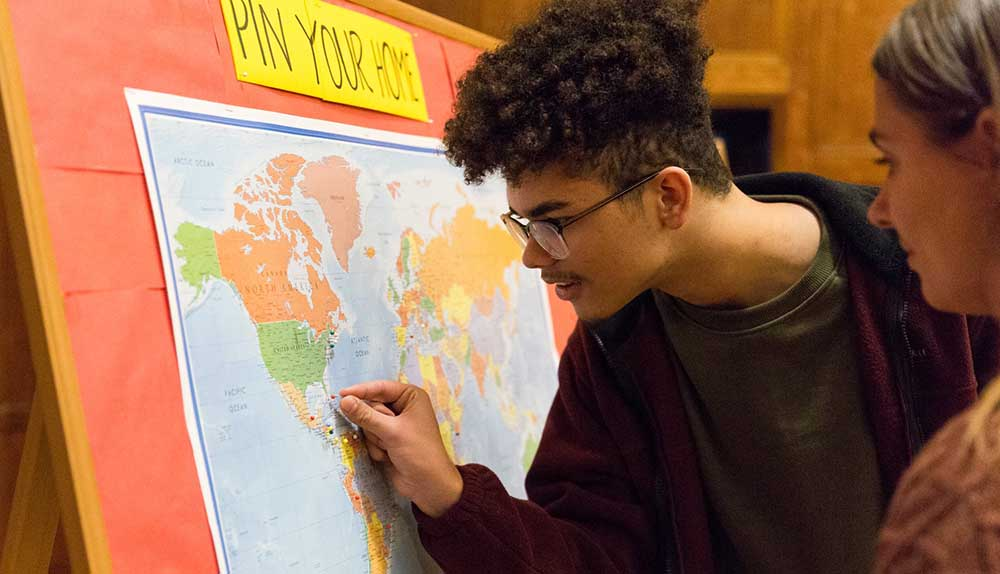 "A student places a pin on a map with the sign ""pin your home"" above it."
