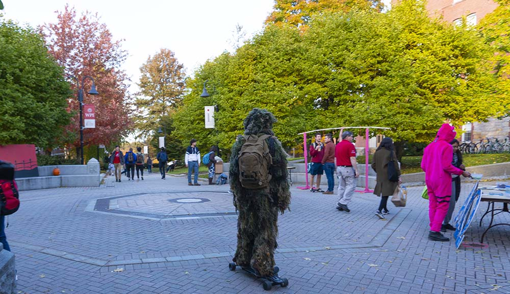 A student dressed in a Swamp Thing Halloween costume rides through the center of campus on a skateboard.