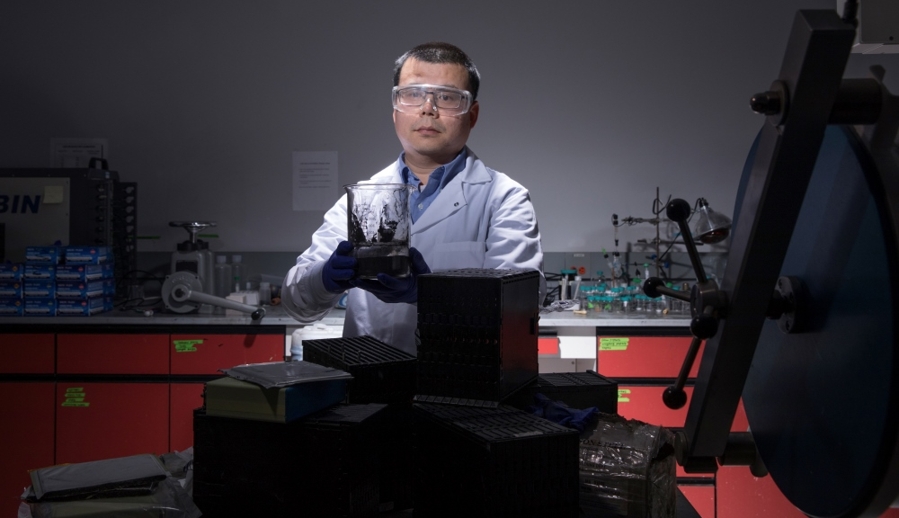 Yan Wang in his lab at WPI with a sample of the cathode materials he is able to produce with his process for recycling lithium-ion batteries. The focus of his work with USABC is electric and hybrid vehicles batteries, like those piled on the lab table.