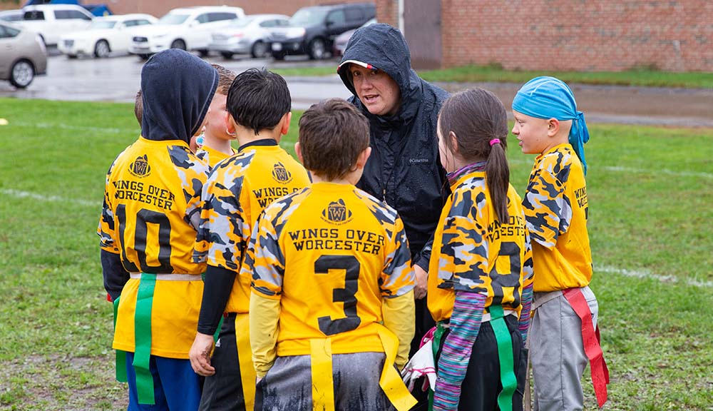 Sustain Roberts huddles with her daughter's flag football team during a game.
