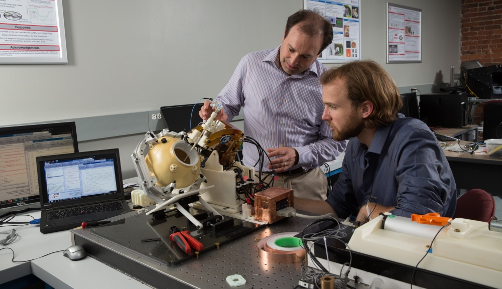 Gregory Fischer, left, and research scientist Christopher Nycz examine a prototype of the MRI-compatible robotic system developed in the first phase of the NIH-funded research program.