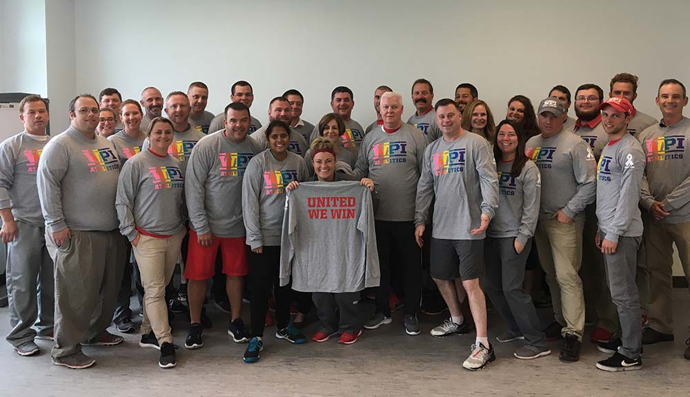 Members of the WPI community gather in the Sports & Rec Center in the new WPI Athletics: United We Win shirts.