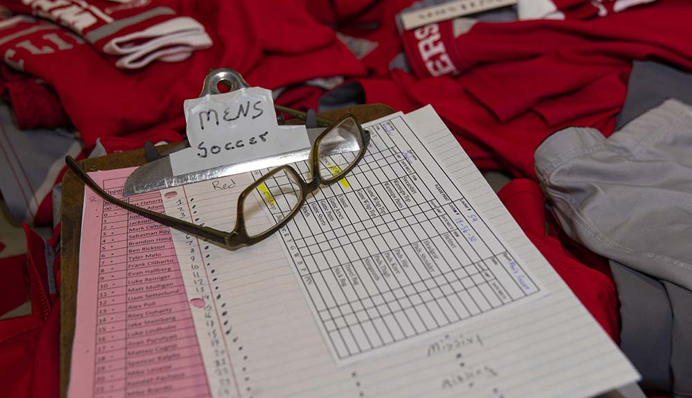 "A close-up photo of McAvey's glasses sitting atop a clipboard with ""Men's Soccer"" written on it, on top of a stack of uniforms."
