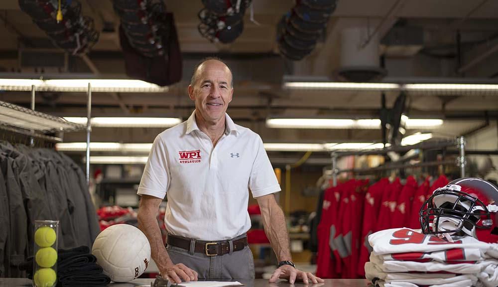 Shawn McAvey stands at the counter of the equipment room with sports equipment around him and behind him.