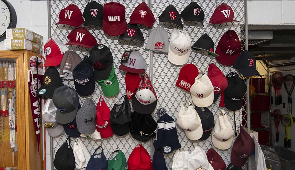 One section of a wall in the equipment room is covered in different kinds of WPI hats from over the years.