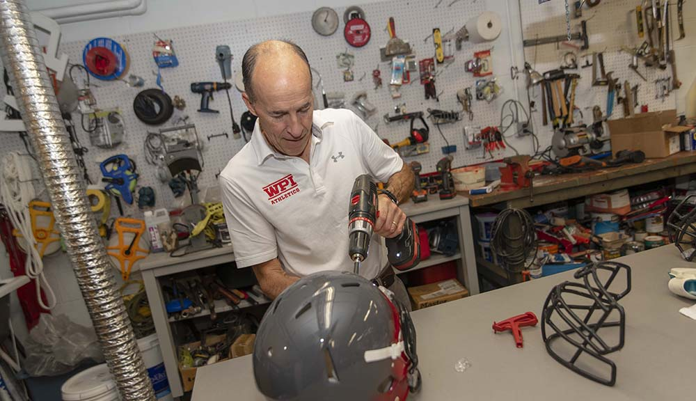 Shawn McAvey makes repairs to a football helmet with an electric drill.