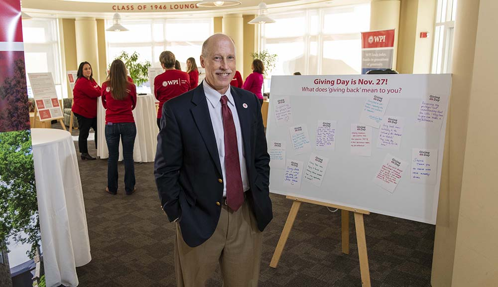 Greg Snoddy stands in the Rubin Campus Center next to a poster board that says