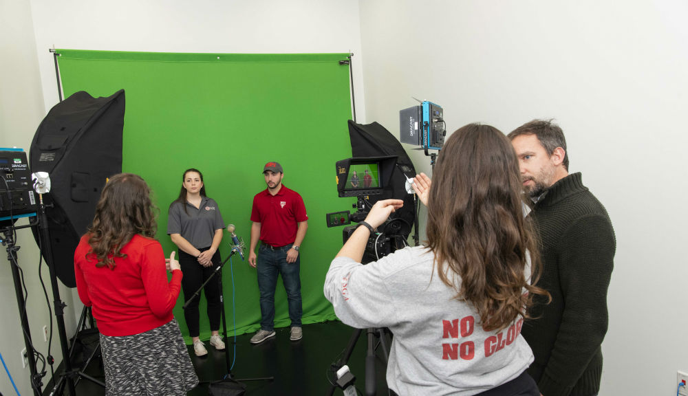 Students and faculty gather in the global media lab with video equipment and a green screen behind them.