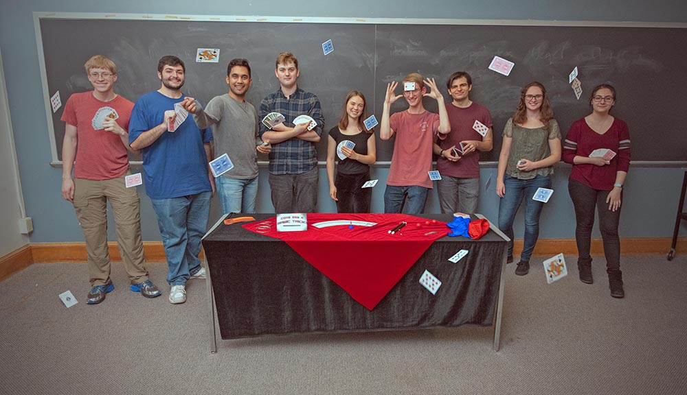 Members of the Society of Magicians student organization stand behind a table and toss playing cards in the air.