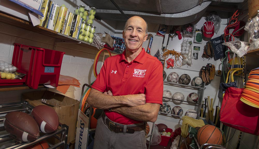 Shawn McAvey stands in the equipment room in front of a variety of sports equipment. He's wearing a red WPI Athletics polo with his arms folded over his chest, and is smiling.