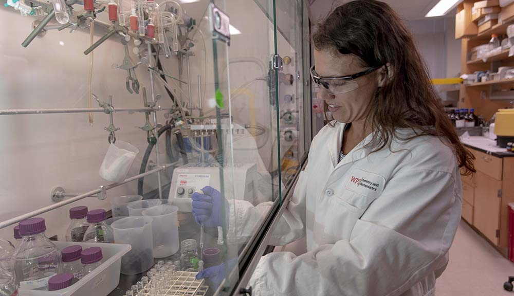 Carissa Olsen completes work in her lab while wearing a white lab coat and safety glasses.