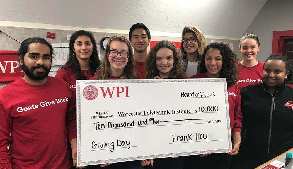 Members of the WPI community hold up an oversized check for $10,000 made out to WPI from Foisie Business School professor Frank Hoy.