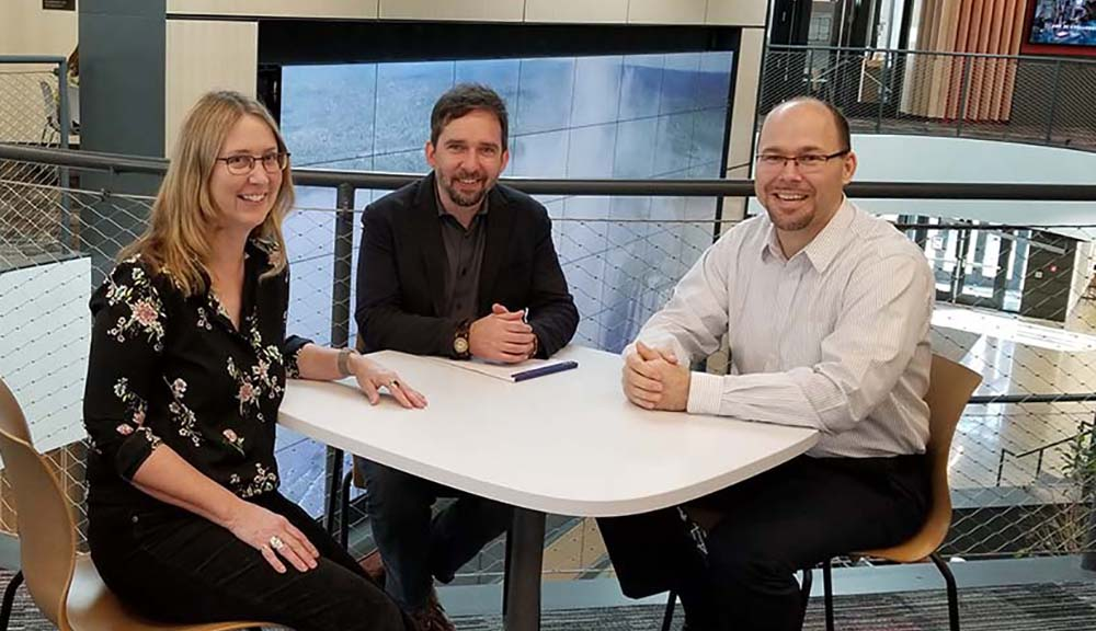 Ingrid Shockey, Stephen McCauley, and Andrew Trapp sit at a table together in the Foisie Innovation Studio.