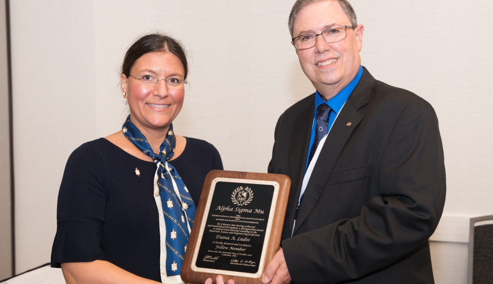 Diana Lados accepts a plaque noting her election as a fellow of Alpha Sigma Mu, the international professional honor society for materials science and engineering, from ASMu president Joe Newkirk at Materials Science & Technology 2018.
