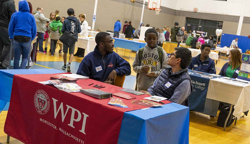 Students sit at a WPI table during a fair to share information about WPI and its programs.