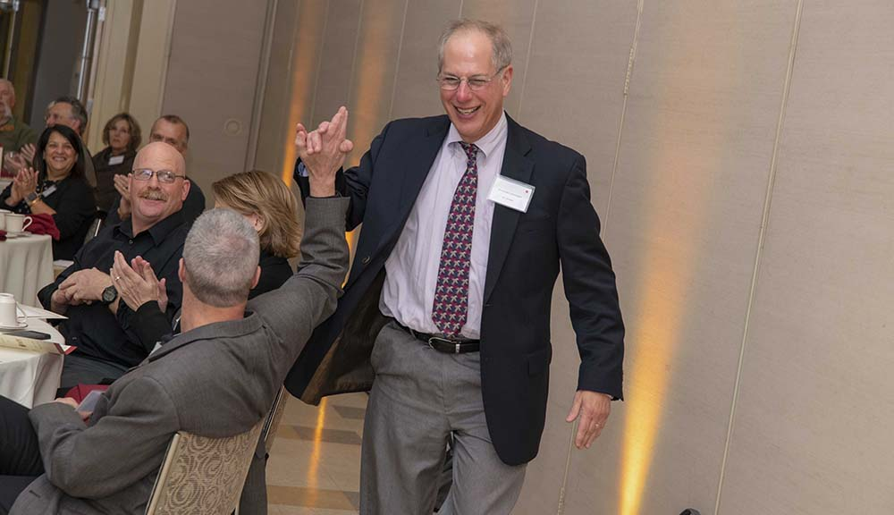 Mike Gennert accepts a high five from one of his peers during the Employee Appreciation Dinner in the Rubin Campus Center Odeum.