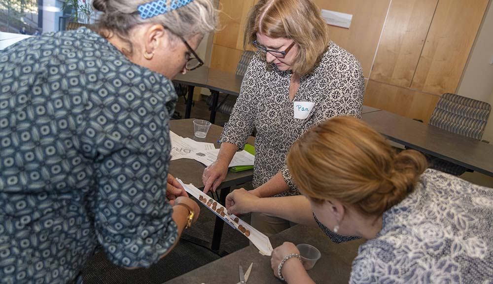 Teachers work together to complete an engineering experiment with paper and pennies during a conference.