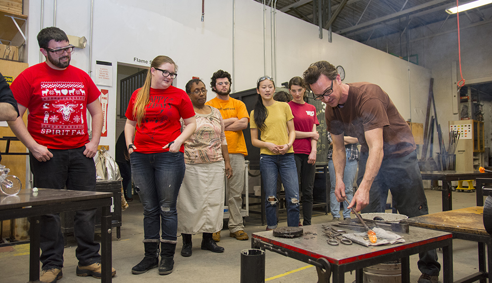 WinterSession participants watch as a member of the Worcester Center for Crafts gives a lesson in glassblowing.