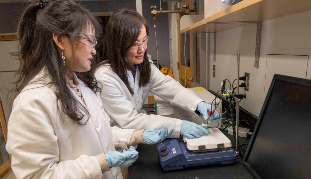 Chemical engineering professor Hong Susan Zhou, right, and PhD candidate Zhiru Zhou prepare a prototype of an electrochemical sensor that can quickly detect the presence of C. diff bacteria, which causes a potentially deadly gastrointestinal infection.