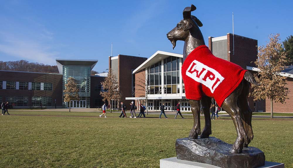 The Proud Goat statue wearing a red sweater with WPI in white letters overlooks the Quad as students walk by.