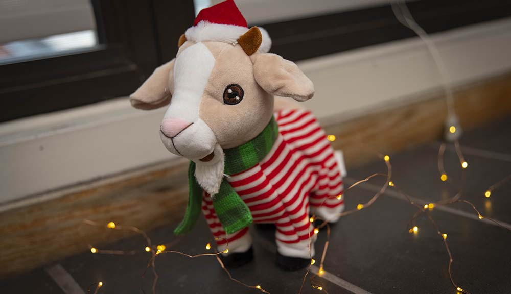 A stuffed animal goat in a sweater, scarf, and Santa hat on a desk with fairy lights underneath him.