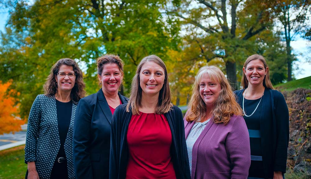 Chrysanthe Demetry, Elizabeth Long Lingo, Jeanine Skorinko, Susan Roberts, and Natalie Farny gather in a group and smile in front of greenery and fall foliage.
