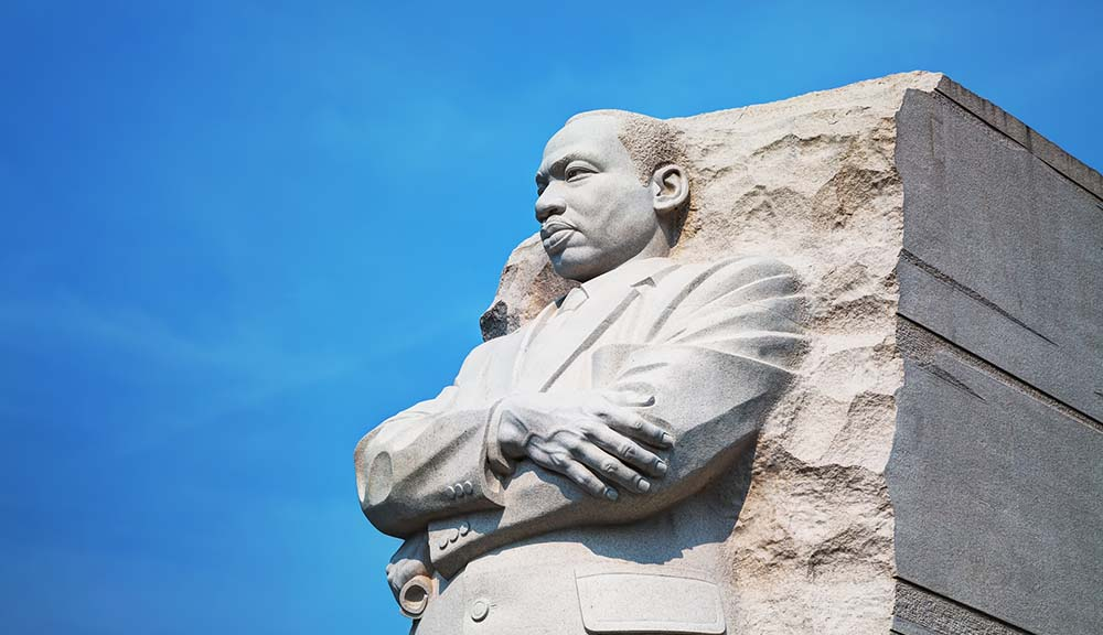 A side profile statue of Dr. Martin Luther King Jr. against a blue background.