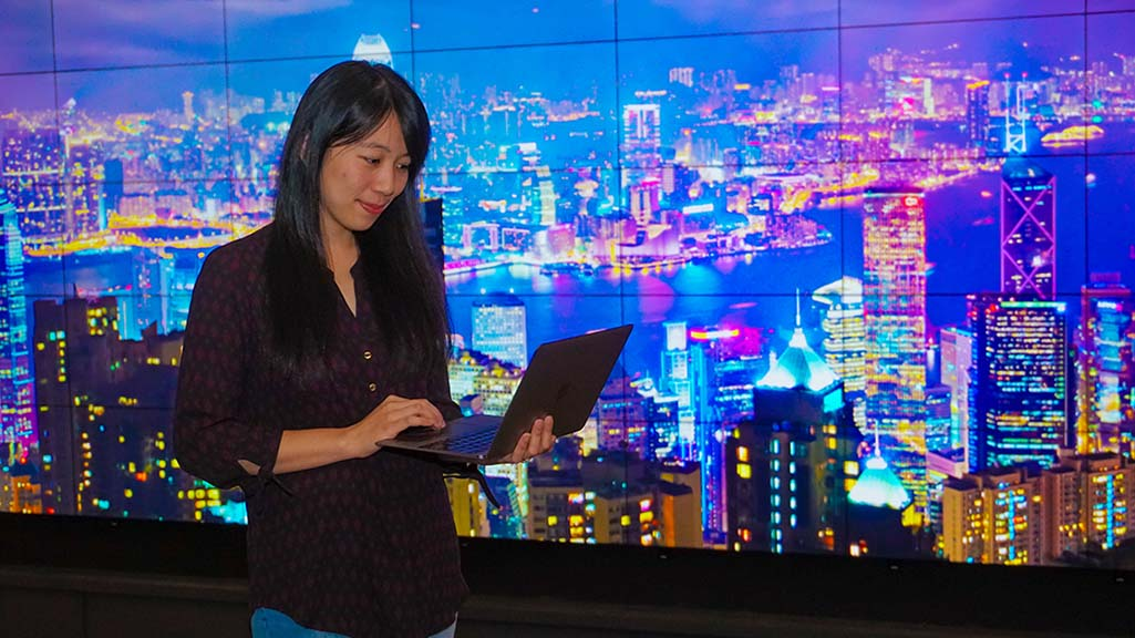 Anny Chang studies information on her laptop with a digital city landscape onscreen behind her in the Foisie Innovation Studio.