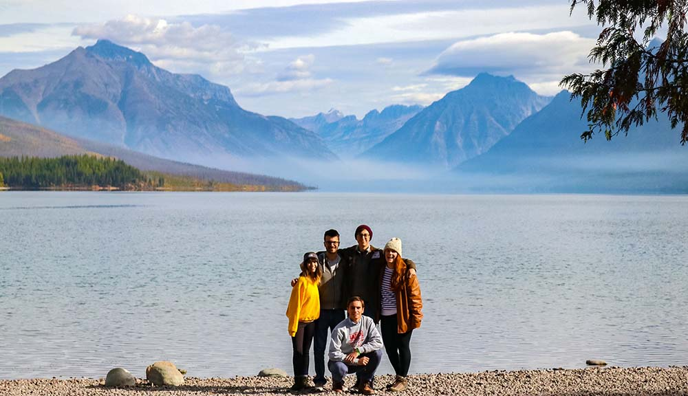 Members of the Glacier National Park Project Center team gather in front of a mountain for a picturesque photo.