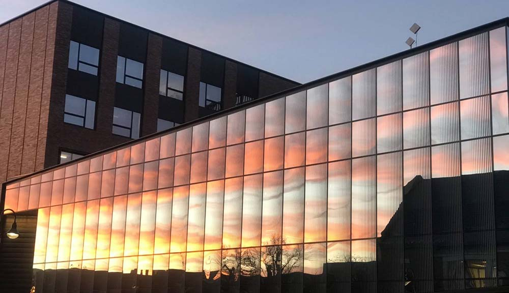 An exterior shot of the sunset shining against the Foisie Innovation Studio.