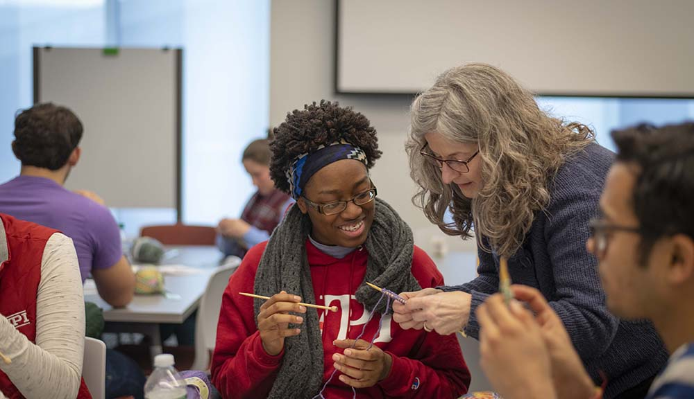 A WPI student learns how to knit in a WinterSession workshop. She's wearing a red WPI sweatshirt and smiling as a teacher assists her.