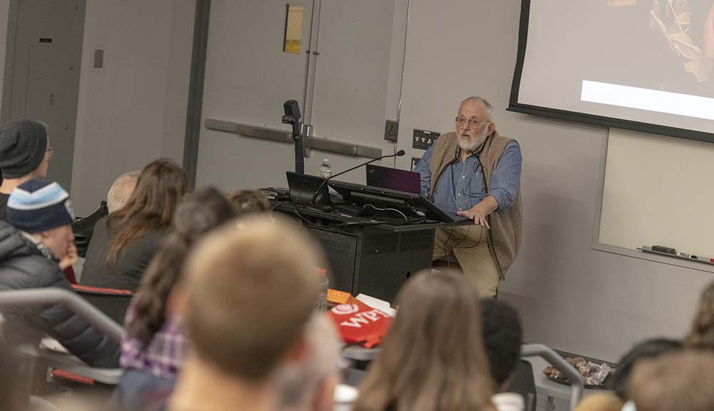 Cleve Moler addresses a crowd of students, faculty, and staff while standing at a podium.