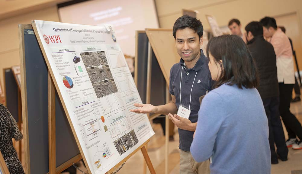 A WPI graduate student presents his work to a GRIE attendee in the Odeum.