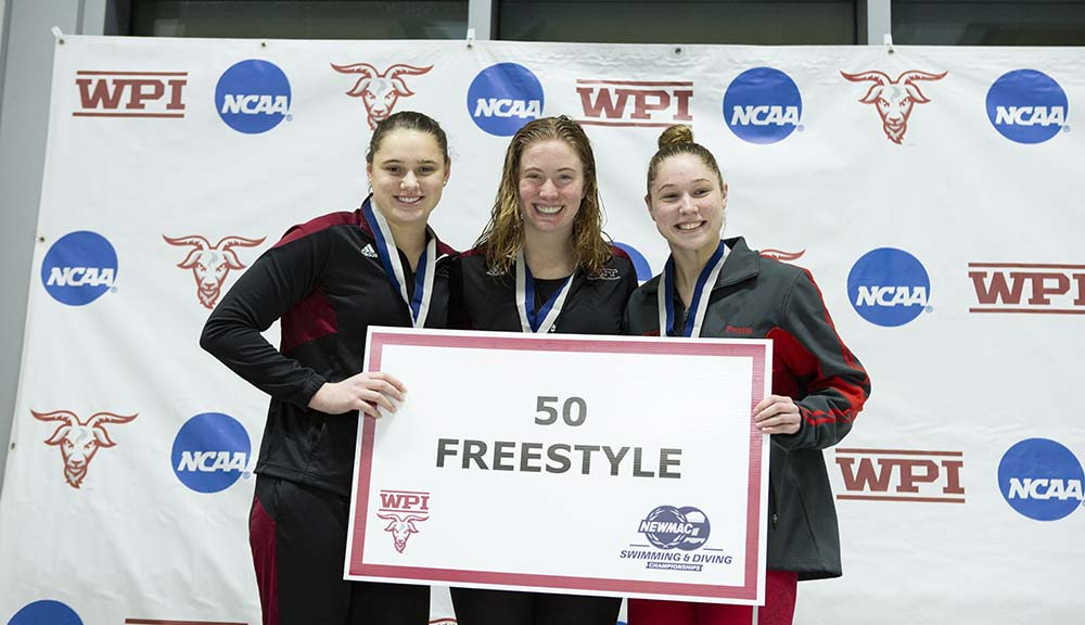 "Katherine Pawlak (right) stands with two other swimmers and holds a sign reading ""50 freestyle."""