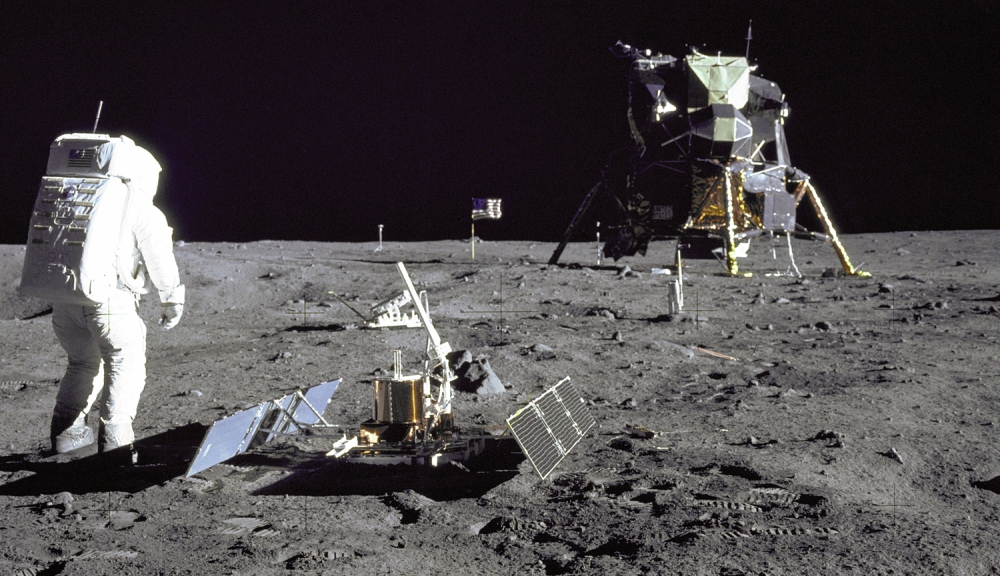 Lunar Module pilot Buzz Aldrin surveys the scene at Tranquility Base in this photo taken in July 1969 by Commander Neil Armstrong. To Aldrin's right is the Passive Seismic Experiment Package, and beyond it is the Laser Ranging Retro-Reflector and the Luna