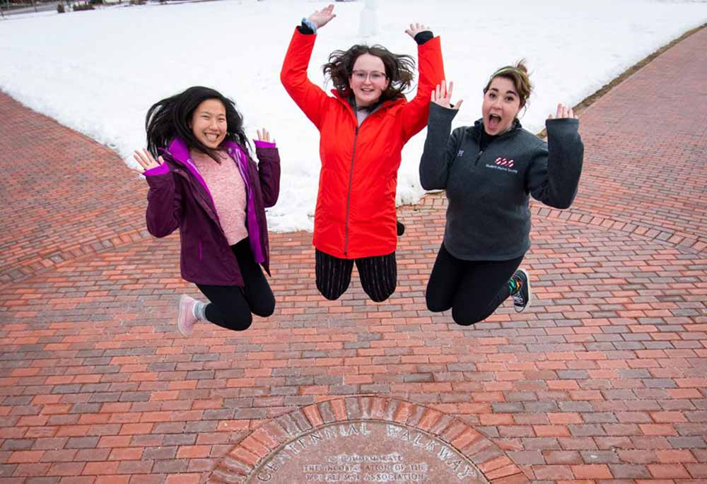 Three students jump over the seal in the middle of the Centennial Walkway.