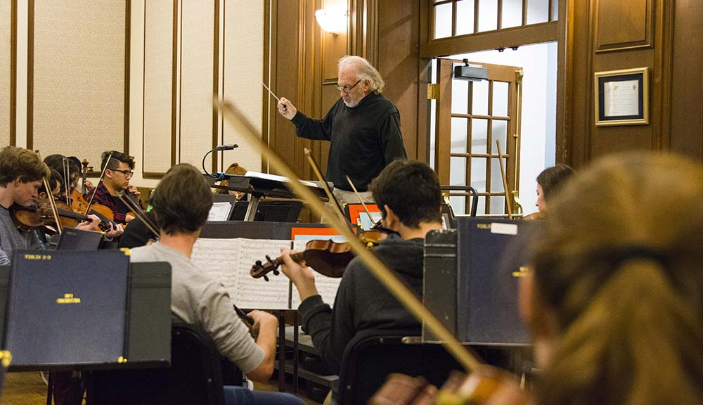 Doug Weeks conducts a group of WPI students during a music practice.