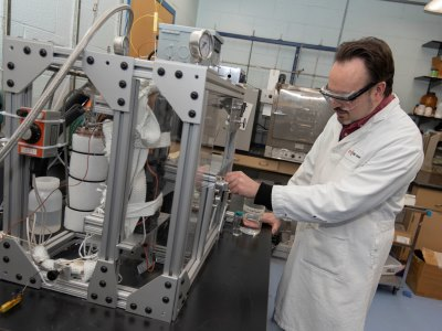 Timko inspects a high-pressure experimental apparatus that was used to measure the recovery of isobutanol into supercritical carbon dioxide alt
