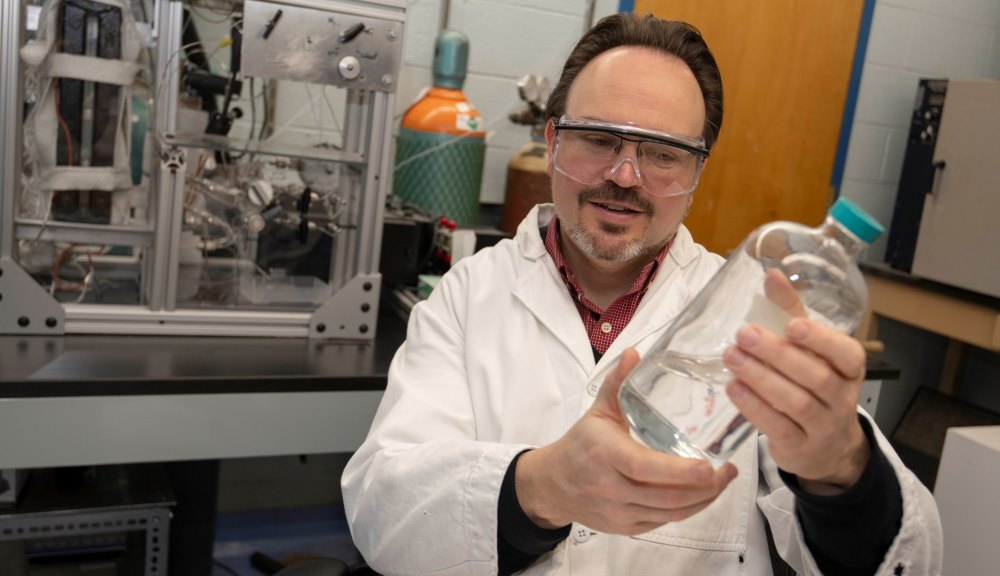 WPI chemical engineering professor Michael Timko with a sample of isobutanol. He is helping develop a novel process that may offer a more economical way to make the biofuel.