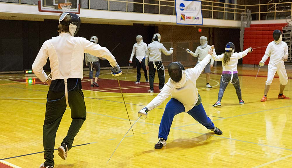 Members of the Fencing Club practice in Harrington Auditorium.