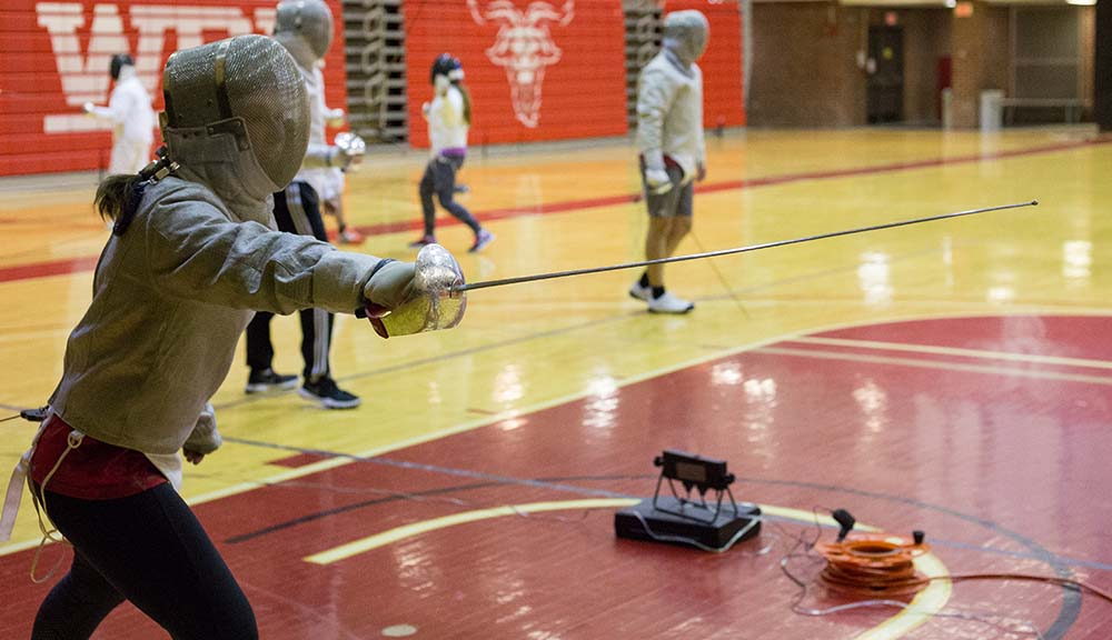 Two members of the Fencing Club during practice in Harrington Auditorium. Several other club members are practicing in the background.