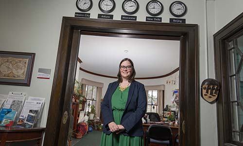 Colleen Callahan-Panday stands in a doorway where clocks displaying the times of different countries are hanging.