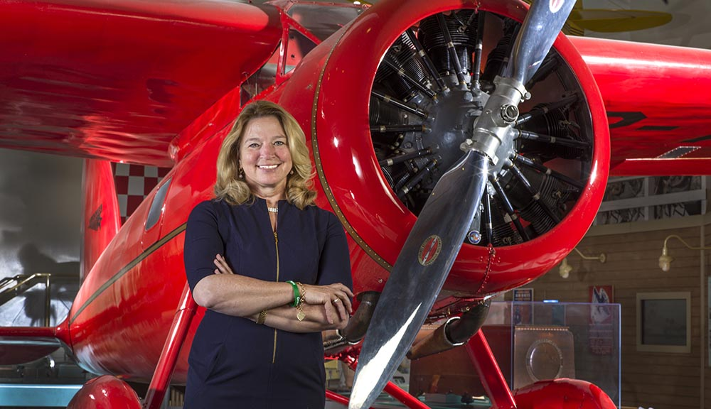Ellen Stofan smiles in front of a red plane, her arms crossed in front of her.