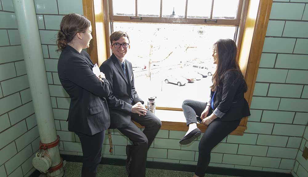Three students take a break, relaxing in front of a window during Project Presentation Day.