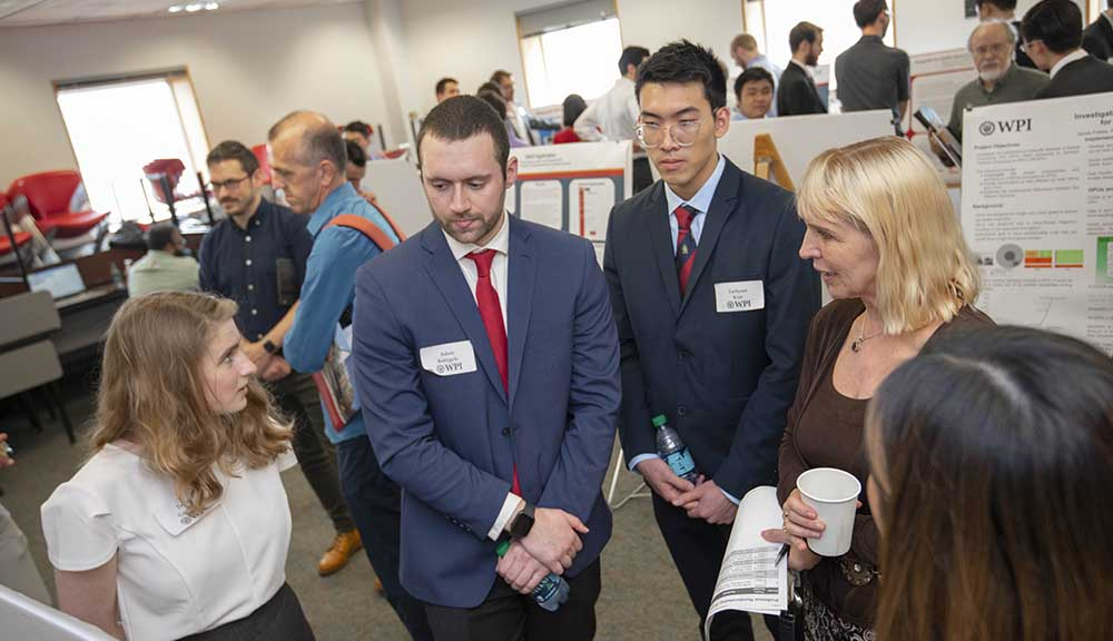 Three students explain their work to an attendee at Project Presentation Day.