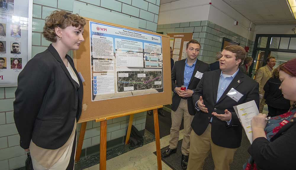 Three students explain their work with a poster presentation during Project Presentation Day.